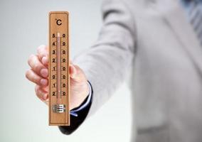 Businessman holding thermomètre lecture haute température photo