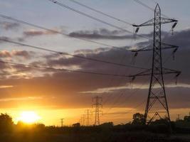 Pylônes électriques dans le champ au crépuscule photo