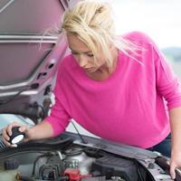 femme inspectant le moteur de la voiture cassée. photo