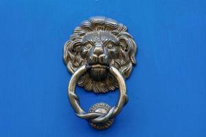 Heurtoir de porte tête de lion sur une porte bleue photo