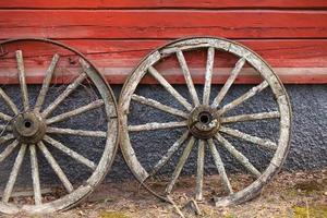 De vieilles roues en bois se tiennent au-dessus du mur rural rouge