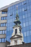 Réflexion de l'église sur la façade en verre moderne photo