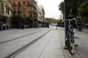 Vélo arrêté à lampost dans la rue urbaine photo