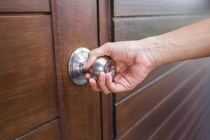 Personne saisissant une poignée de porte d'argent sur la porte en bois photo
