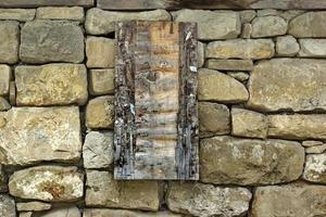Panneau en bois vintage sur le vieux mur de pierre