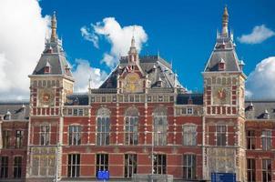 Façade de la gare centrale d'Amsterdam en journée ensoleillée, aux Pays-Bas.