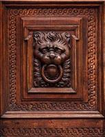 Tête de lion comme sculpture sur bois dans la vieille porte photo