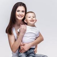heureuse mère avec un enfant sur fond gris clair photo