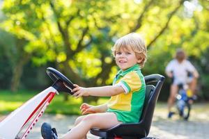 Petit garçon actif conduisant une voiture à pédales dans le jardin d'été