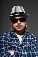 expressif jeune homme aux cheveux blonds portant chapeau et lunettes de soleil.