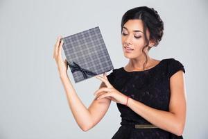 Portrait d'une belle femme mignonne tenant une boîte-cadeau photo