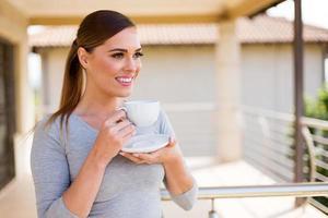 femme réfléchie tenant une tasse de café photo