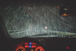 neige et autoroute vu à travers le pare-brise de voiture photo