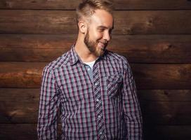 portrait de jeune bel homme positif contre le vieux mur en bois. photo