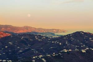 montagnes et lune à l'heure d'or photo