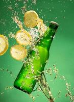 bouteille de bière verte avec des éclaboussures de liquide photo