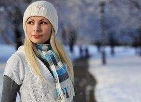 Femme d'hiver avec bonnet tricoté sur les arbres d'allée avec de la neige photo