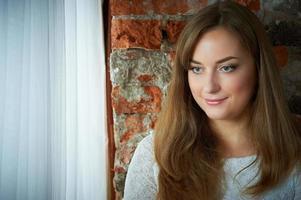 jolie jeune fille contre un mur de briques photo