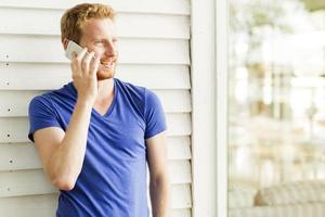 Heureux bel homme aux cheveux rouges à l'aide de téléphone et souriant