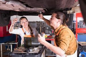 deux mécaniciens réparant une voiture photo