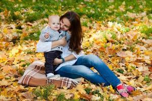 Bébé garçon en pull jouant avec sa mère parmi pumpki photo