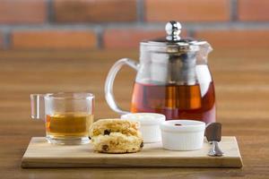 table de petit-déjeuner avec thé, théière, confiture, pain et hon photo