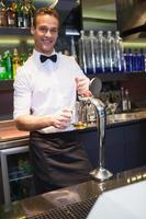 Beau barman tirant une pinte de bière photo