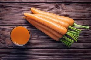 Vue de dessus du jus de carotte frais sur fond de bois