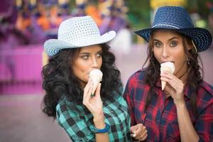 deux belles filles en chapeaux de cow-boy mangeant de la glace