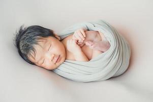 Bébé nouveau-né asiatique enveloppant dans un cocon endormi