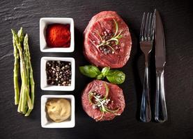 Steaks de boeuf cru frais sur pierre noire