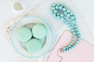Macaron à la menthe et perles sarcelle sur fond clair photo