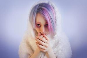 fille inhabituelle aux cheveux roses, se sentir froid en manteau de fourrure photo