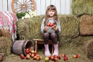Portrait de jeune fille villageoise avec panier de pommes dans la grange photo