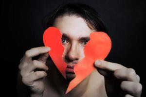 visage de jeune bel homme avec coeur de papier brisé photo