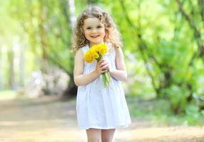 portrait de printemps ensoleillé d'adorable petite fille mignonne souriante avec photo