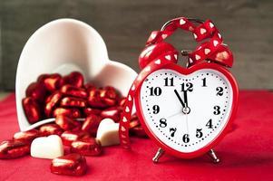 horloge d'amour rouge en forme de coeur d'amour de valentine avec des chocolats sucrés. photo