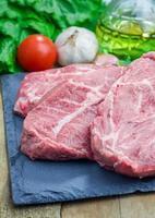 Steak de boeuf cru sur un plateau en ardoise noire photo