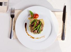 Plat principal de viande garni gastronomique sur assiette photo