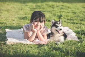 belle fille asiatique couchée sur l'herbe verte avec un sibérien photo