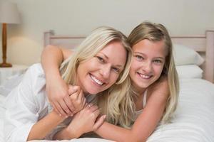 mère aimante et fille couchée dans son lit photo
