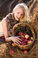 Belle blonde femme souriante avec des pommes dans le panier à la ferme photo