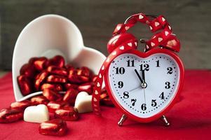 horloge d'amour rouge en forme de coeur Saint-Valentin avec chocolats photo