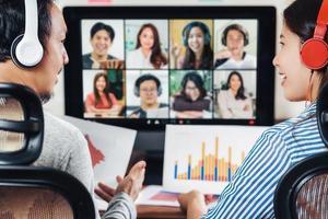 Vue arrière des partenaires asiatiques travaillant sur une réunion en ligne photo