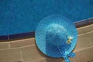 chapeau de plage à côté de la piscine