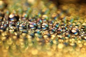 Macro de gouttes d'or de l'eau sur une surface de DVD