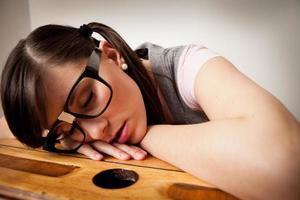 étudiant de jeune femme ennuyé et ringard dormant sur le bureau de l'école photo