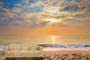 Fauteuil-fauteuil en tissu sur coucher de soleil sur la plage tropicale photo
