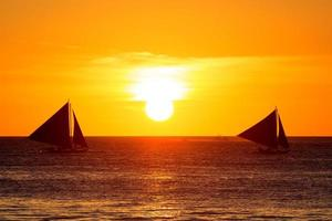 voiliers au coucher du soleil sur une mer tropicale. photo de silhouette.