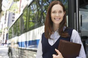 femme d'affaires souriante avec portefeuille en bus photo